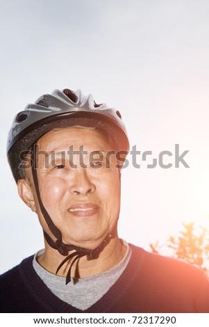 A shot of a senior asian man wearing a bike helmet - stock photo