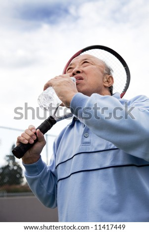 A shot of a senior asian tennis player drinking water while resting - stock photo