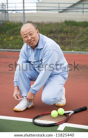 A shot of a senior asian tennis player tying up his shoes - stock photo