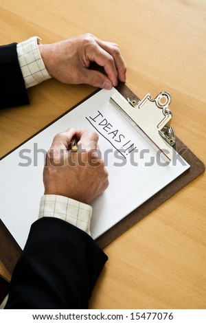 A shot of a senior businessman brainstorming and writing ideas on the paper