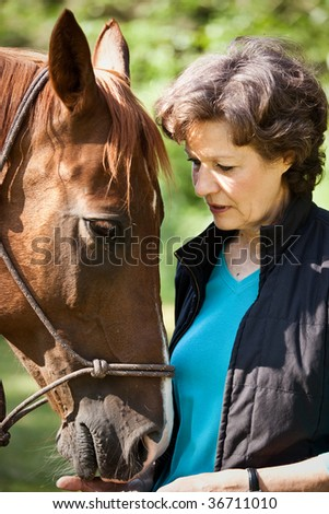 A shot of a senior caucasian woman with her horse - stock photo
