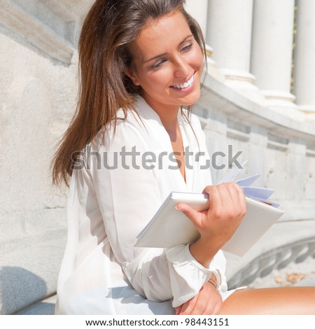 A shot of a smiling college student reading a book at park - stock photo