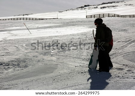 A shot of a  snowboarder watching the slopes - stock photo