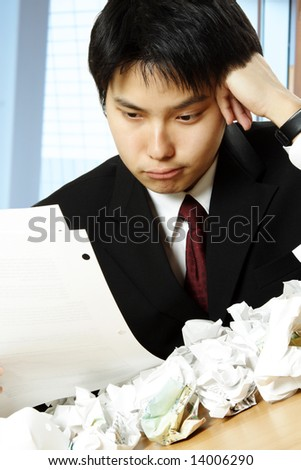 A shot of a stressed asian businessman working hard in the office with paper all over the table - stock photo