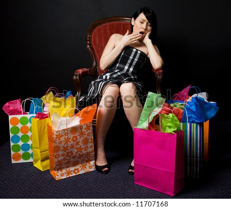A shot of a tired and exhausted beautiful woman after shopping - stock photo