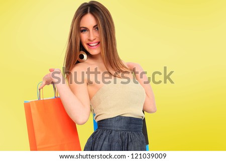 A shot of a woman with bags shopping over yellow background - stock photo