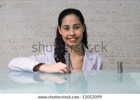 A shot of a young businesswoman in suit at glass desk with quarters on it. - stock photo