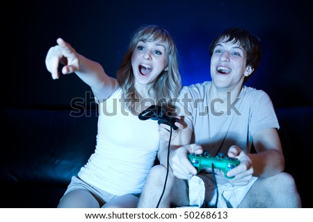 A shot of a young couple playing video games in the living room - stock photo