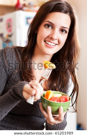 A shot of a young woman holding a fruit bowl