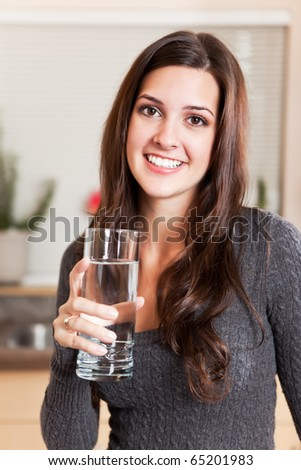 A shot of a young woman holding a glass of water