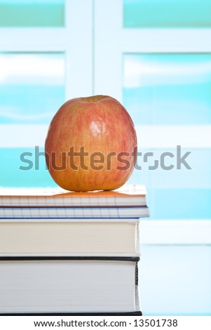 A shot of an apple on top books in a classroom
