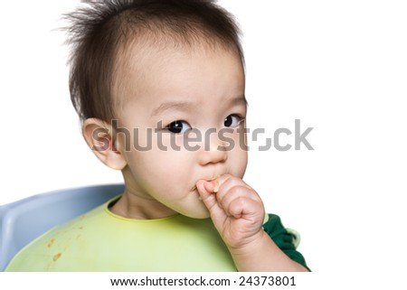 A shot of an asian baby during feeding time - stock photo