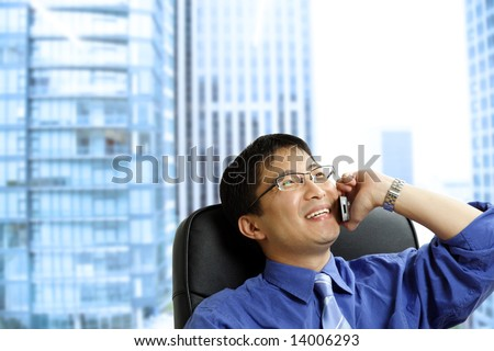 A shot of an asian businessman talking on the phone at the office - stock photo