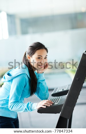 A shot of an Asian college student using a computer kiosk - stock photo