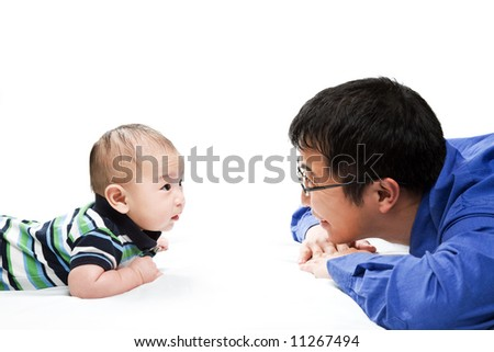 A shot of an asian father playing with his son - stock photo