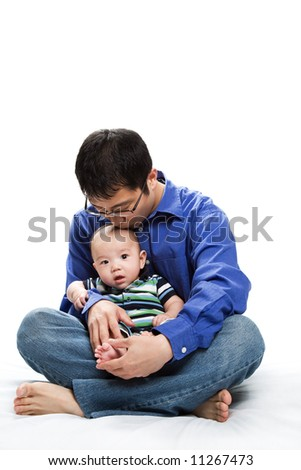 A shot of an asian father with his baby son - stock photo