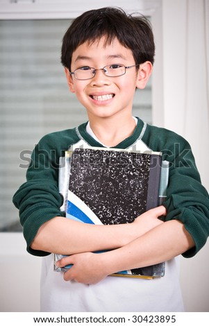 A shot of an asian kid carrying books