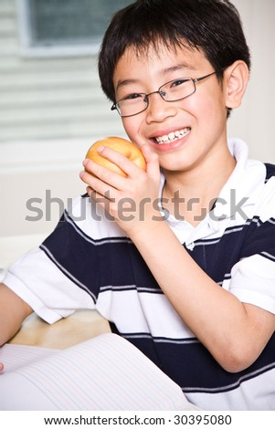 A shot of an asian kid studying and eating an apple at home - stock photo