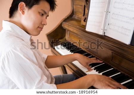 A shot of an asian man playing piano - stock photo