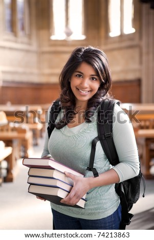 A shot of an asian student carrying books in a library - stock photo