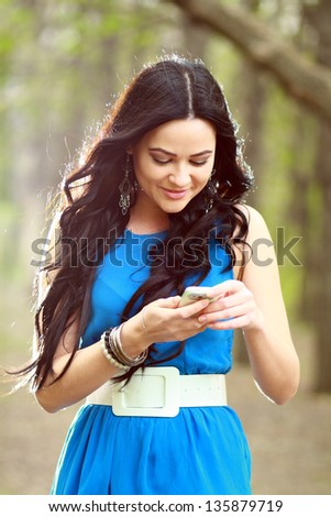 A shot of an Asian student girl texting on the phone - stock photo