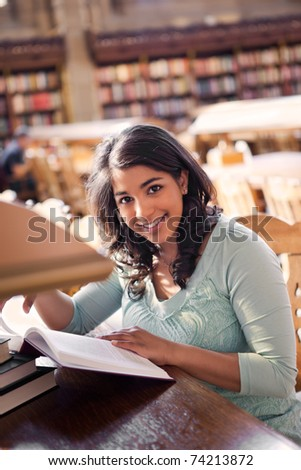 A shot of an asian student studying in a library - stock photo