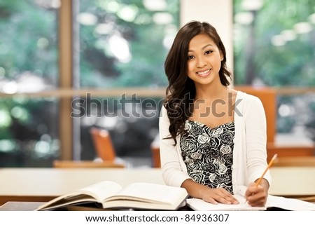 A shot of an Asian student studying in the library - stock photo