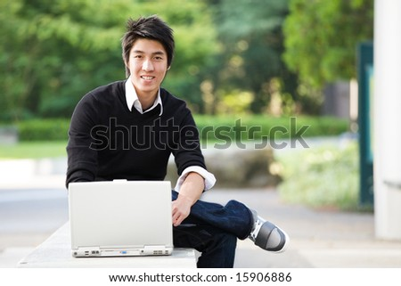 A shot of an asian student studying on his laptop - stock photo