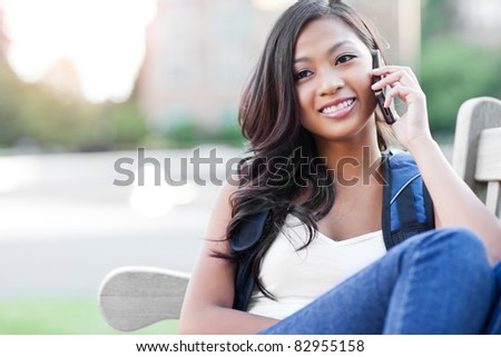A shot of an Asian student talking on the phone - stock photo