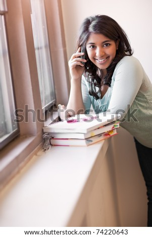 A shot of an asian student talking on the phone in the library - stock photo