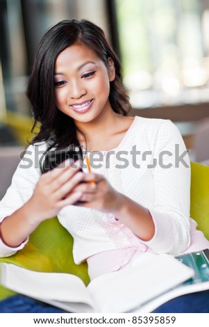 A shot of an Asian student texting on the phone on campus - stock photo