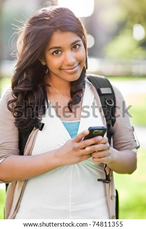 A shot of an asian student texting with her cellphone on campus - stock photo