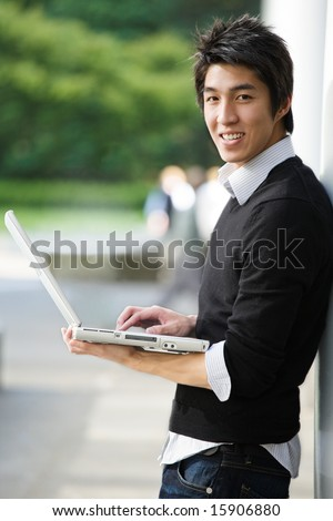 A shot of an asian student working on his laptop at the campus - stock photo