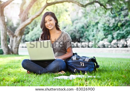 A shot of an Asian student working on laptop on campus - stock photo
