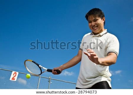 A shot of an asian tennis player hitting a tennis ball - stock photo