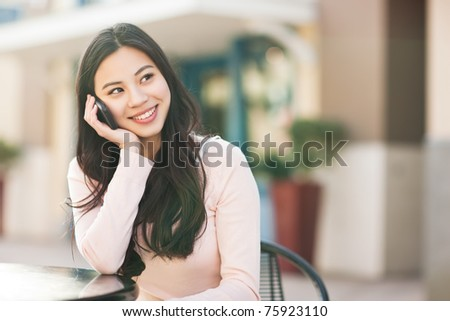 A shot of an asian woman talking on the phone