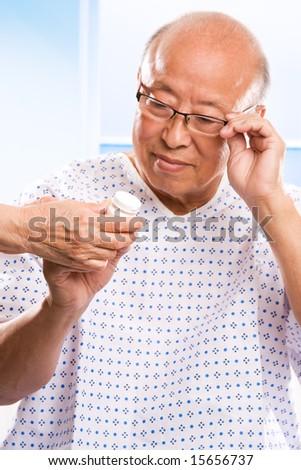 A shot of an elderly asian man examining his prescription - stock photo