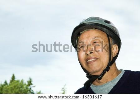 A shot of an elderly asian man wearing a bike helmet - stock photo