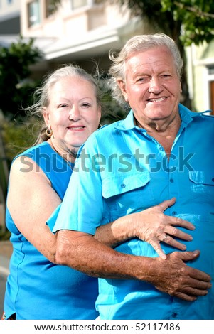 a shot of an elderly lady with her hands around an elderly man outdoors
