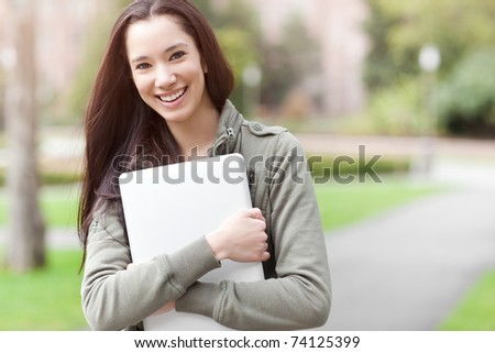 A shot of an ethnic college student carrying a laptop on campus - stock photo