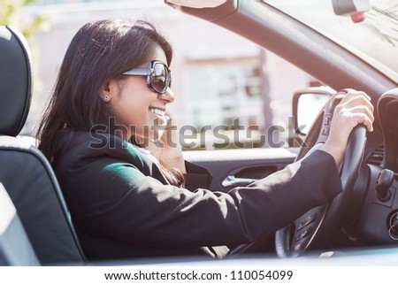 A shot of an Indian businesswoman driving a car and talking on the phone - stock photo