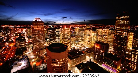 A SHOT OF AN URBAN CITY AT SUNSET WITH ALL LIGHTS LIT UP - stock photo