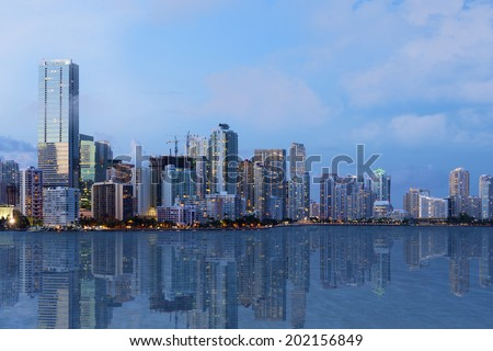 A shot of beautiful Downtown Miami skyline after sunset with reflection in the water. All logos and advertising removed.