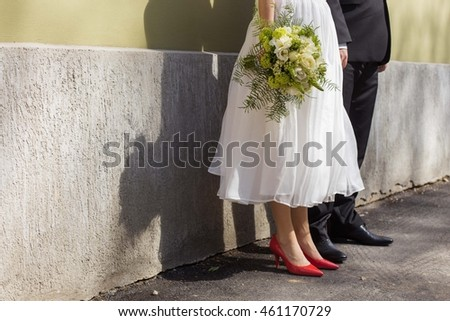 a shot of bride and groom's feet leaned against a wall on a sunny wedding day