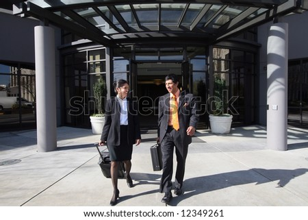 A shot of businessman and businesswoman walking out of building on sunny day. - stock photo