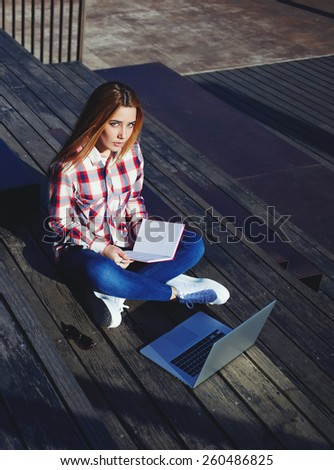 A shot of caucasian college student studying with book and laptop computer at campus, attractive young woman using laptop sitting on wooden staircase enjoying sunny day outdoors, female freelancer - stock photo
