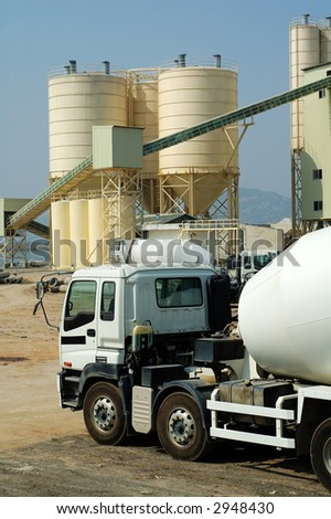 A shot of cement factory with mixer trucks - stock photo