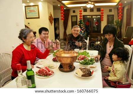 A shot of Chinese family at dinner table - stock photo