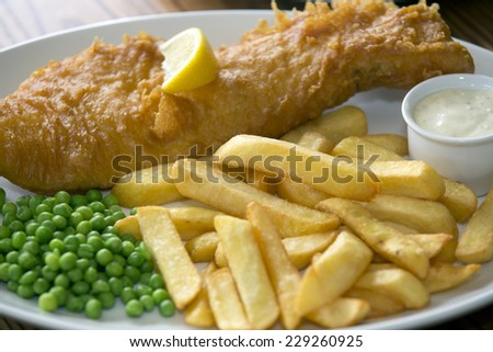 A shot of Fish and Chips on pub table - stock photo