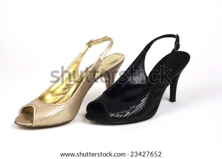A shot of one gold, and one black women's high-heel dress shoe against white background - stock photo